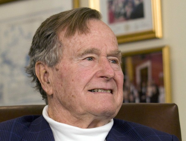 Former U.S. President George H.W. Bush listens to Republican presidential candidate Mitt Romney in Houston, Texas, in this March 29, 2012 file photo.