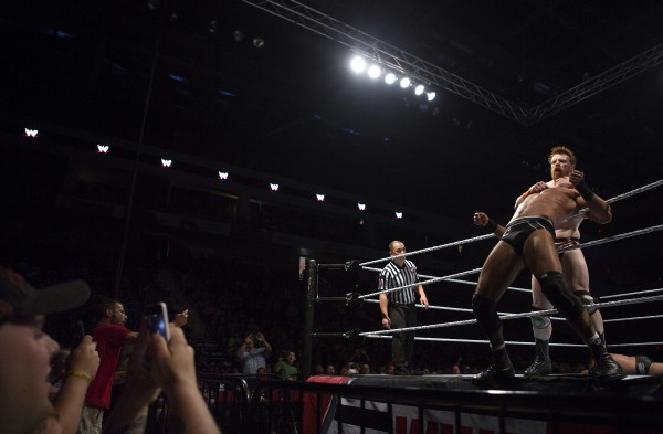 Fans take photos as Sheamus (right) chocks Cesaro during WWE Live in Bangor Saturday at the Cross Insurance Center.