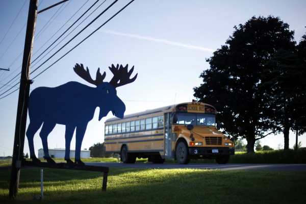 A school bus passes a silhouette of a moose in front of the Blue Moose restaurant on Route 1 in Monticello, Maine.