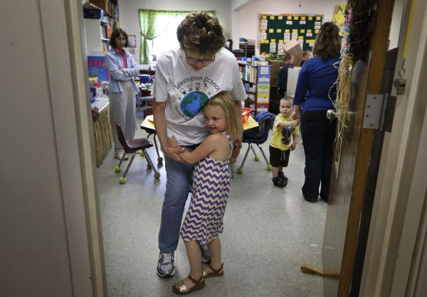 Kindergarten teacher Susan McMann gets a hug from a student as school is dismissed for the final time at the Wellington public school in Monticello, Maine, Tuesday, June 17, 2014.