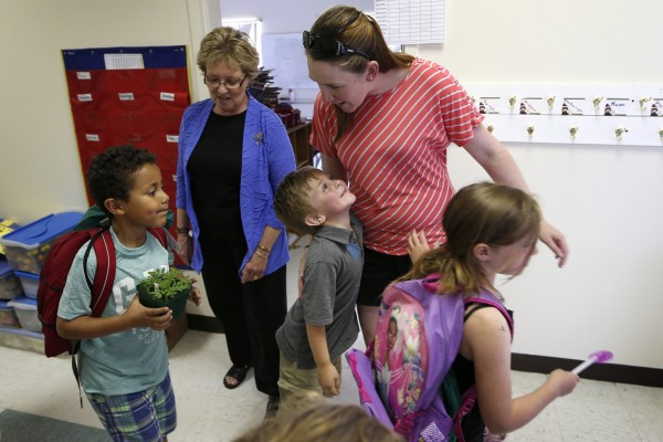 Kindergartner Russell Emery, center, gives a big to teacher's assistant Ashley Porter on the final day of school at the Wellington public school in Monticello, Maine, Tuesday, June 17, 2014.