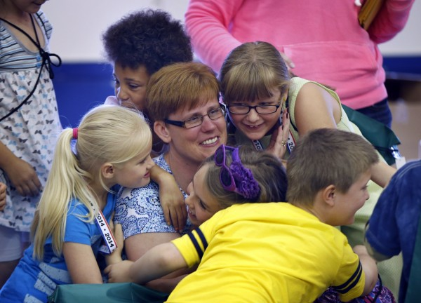 Pre-K teacher Crystal Folsom gets a hug from first-graders on the last day of school in Monticello.