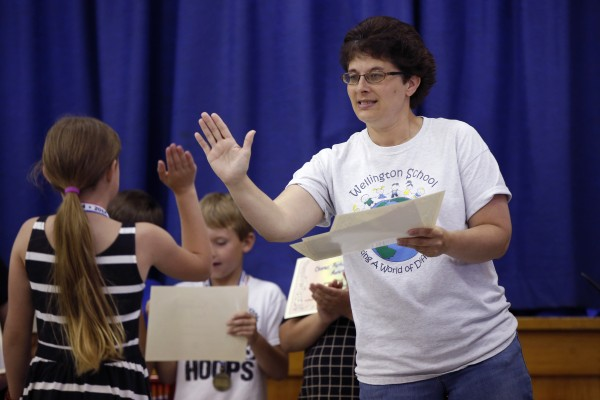 Principal Cindy Peterson slaps a high-five while handing out awards at an assembly on the final day of school at the Wellington public school in Monticello, Maine, Tuesday, June 17, 2014.