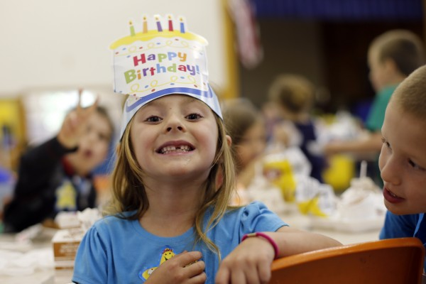 Birthday girl Anna Foreman shows off a missing tooth during lunchtime at the Wellington public school in Monticello, Maine.
