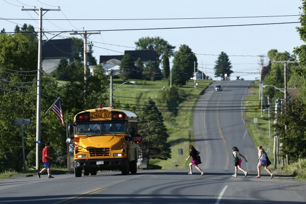 Students run to school on Route 1 on their way to the Wellington public school in Monticello, Maine.