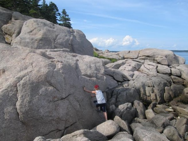 Henry Westrich climbs a big rock along the boulder-strewn shore of Great Wass Island.
