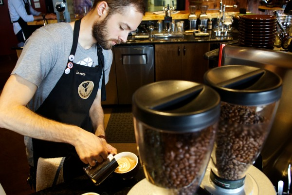 Barista James Frydrych slings java behind the counter at Coffee By Design on Diamond Street in Portland on Friday morning.