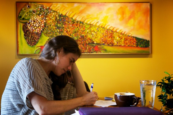 Elise Damboise writes and drinks a cup of joe at Coffee By Design on Diamond Street in Portland on Friday morning.
