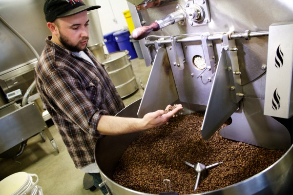 Roaster Asa Korsen checks the hot beans beans as they come off the heat at Coffee By Design on Diamond Street in Portland on Friday.