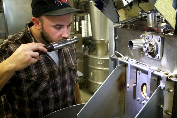 Asa Korsen, a coffee roaster at Coffee By Design on Diamond Street in Portland, checks the progress of roasting beans by sniffing a sample on Friday.