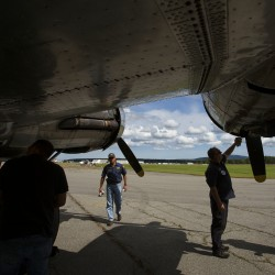 Flight crew members wipe oil of the underside of the Sentimental Journey, a fully restored B-17 Flying Fortress, after a trip over Bar Harbor Tuesday at the Hancock County-Bar Harbor Airport in Bar Harbor.