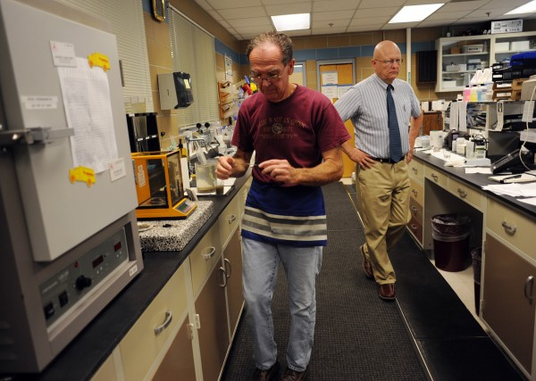Tom Hambrock, labratory director, takes a prepared slide to a microscope.  Bradley Moore (background), superintendent of the Wastewater Treatment Plant, said that 58 tons of grease per year is removed from the plant.