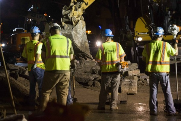 Workers clean up after what local media describe as a stone facade collapsed underneath the Brooklyn Bridge after an unusually strong summer storm in New York July 2, 2014.