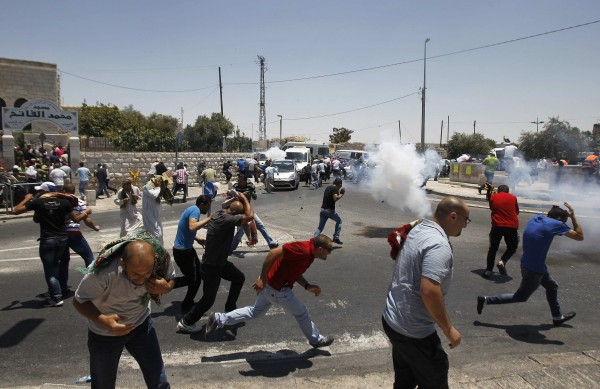 Palestinian protesters run away from tear gas fired by Israeli soldiers during clashes after Friday payers in the Arab east Jerusalem neighbourhood of Ras al-Amud.