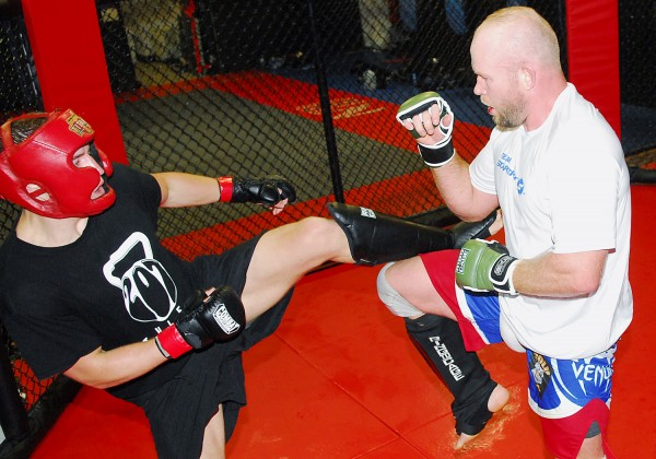 Tim Boetsch (right) blocks a kick from a sparring partner during a workout Saturday at the Team Irish gym in Brewer. Boetsch is training with Marcus Davis for an August UFC fight at the Cross Insurance Center in Bangor.