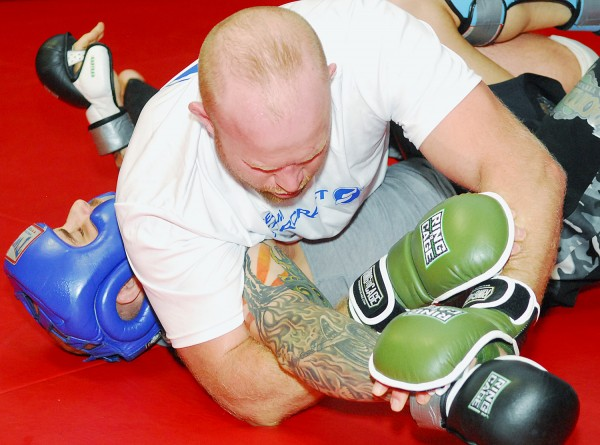 Mixed martial arts fighter Tim Boetsch holds down a sparring partner during a training session Saturday at the Team Irish gym in Brewer. Boetsch is training with Marcus Davis for an August UFC bout at the Cross Insurance Center in Bangor.