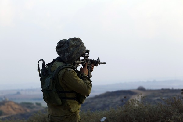 An Israeli soldier holds up his weapon outside the northern Gaza Strip on Monday.