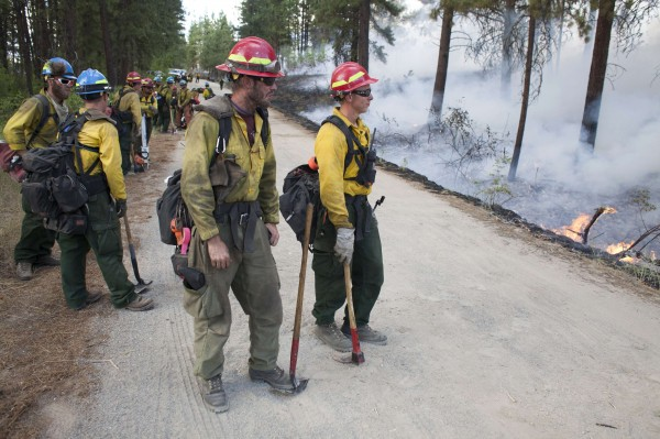 Firefighters keep watch over a controlled burn while battling the Carlton Complex Fire near Winthrop, Washington on July 19, 2014.