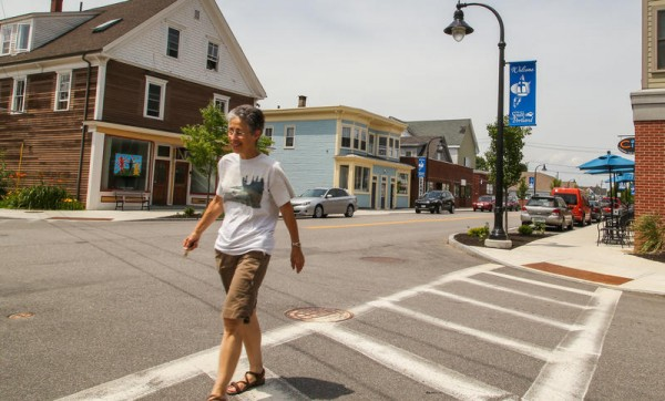 South Portland resident Karen Silverman crosses the intersection of Ocean and D streets Tuesday. She said the block between C and D streets has undergone substantial changes in the decade since she moved to the city. &quotIt feels like a real neighborhood now,&quot she said. &quotIt makes you want to buy local.&quot