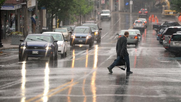 A man crosses Main Street in Bangor in the pouring rain Tuesday morning.