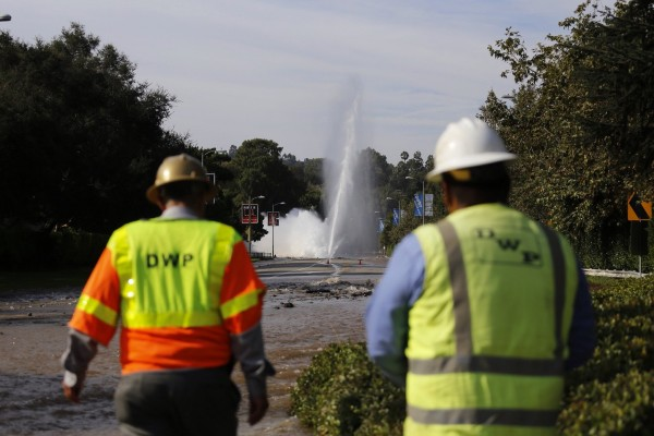 Utility workers view a water main break on Sunset Boulevard near the UCLA campus in Los Angeles on Tuesday, July 29, 2014.