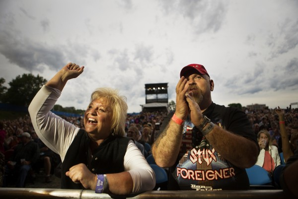 Carol Naro (left) and Hollis Seamans cheer during the Styx, Foreigner and Don Felder show Saturday at the Darling's Waterfront Pavilion in Bangor.