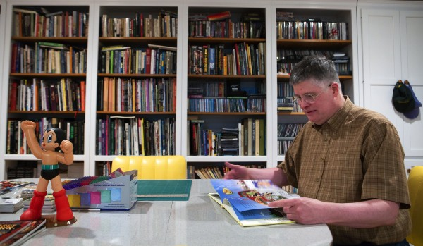 Maine-based author/illustrator Mark Scott Ricketts reads a page from his new children's book &quotAdventures in Vacationland&quot Thursday at his home in Bangor. A former comic book illustrator, Ricketts recently decided to try his hand at children's books.