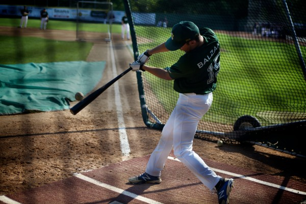 Sam Balzano, a University of Maine outfielder from Portland, puts the bat on the ball while taking practice swings before a Sanford Mainers game at Goodall Park on Monday afternoon.