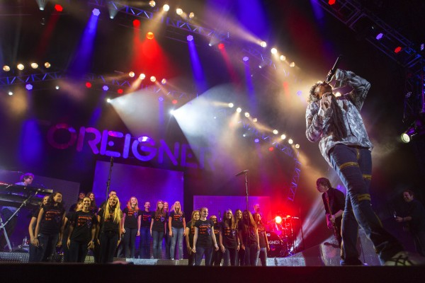 Foreigner's Kelly Hansen (right) belts out a song with the Hermon High School Choir during the Styx, Foreigner and Don Felder show Saturday at the Darling's Waterfront Pavilion in Bangor.