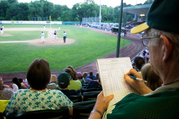 Sam Demeritt keeps score at the Sanford Mainers game Monday night. As a senior citizen, his ticket cost just $3.