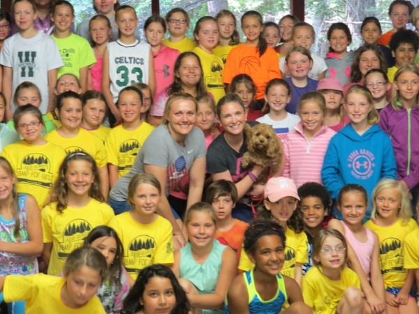 Julia Clukey (center) and WCHS-TV of Portland news reporter Jackie Ward (holding dog) take part in a group photo with participants at Clukey's Camp For Girls in June at Maranacook Lake in Readfield.