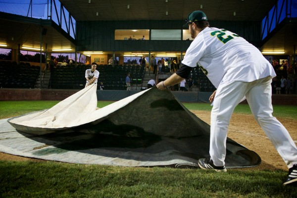 After the game, Sanford Mainers Steven Bermen (left) and Ryan Johnson help the grounds grew replace the tarps at Goodall Park.