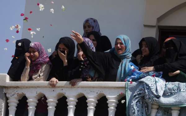 Relatives of Palestinian Hamas militant Abdulrahman al-Zameli throw flowers as they mourn during his funeral in Rafah in the southern Gaza Strip on Monday.