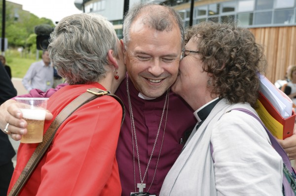 Bishop of Gloucester Michael Perham hugs female clergy members after the Synod session which approved the consecration of women bishops, in York on July 14, 2014.