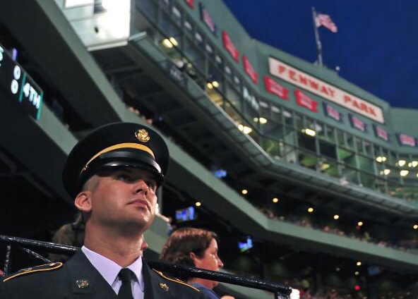 Bucksport native Ben Arnold stands on the Red Sox dugout while being honored as part of the Boston Red Sox's &quotHats Off to Heroes&quot program at Fenway Park in Boston during the game against the Chicago Cubs on Wednesday night. The 29-year-old Arnold is a highly-decorated soldier who served in the Navy and is now in the Army National Guard.