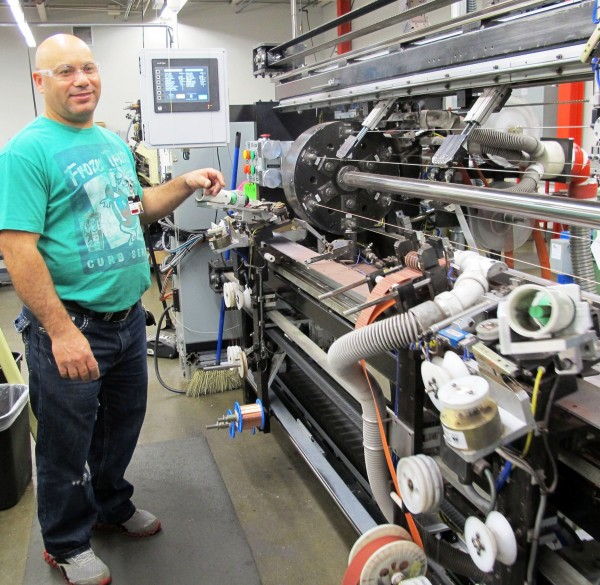 D'Addario & Co.'s string-making plant in Farmingdale, NY, churns out more than 700,000 strings a day over three shifts. A worker watches over the largely automated machine.