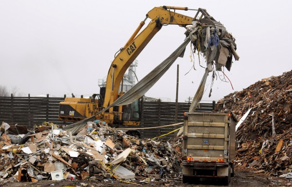 An excavator loads processed demolition debris at a landfill.