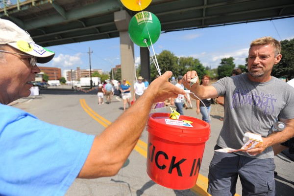 Jim Poole of Kenduskeag (right) drops money into a donation bucket held by festival volunteer David Pelkey during the 2012 American Folk Festival in Bangor on Saturday, Aug. 25, 2012. Poole and his girlfriend Jessica Paschal said people who enjoy the festival and want it to happen again should all donate money.