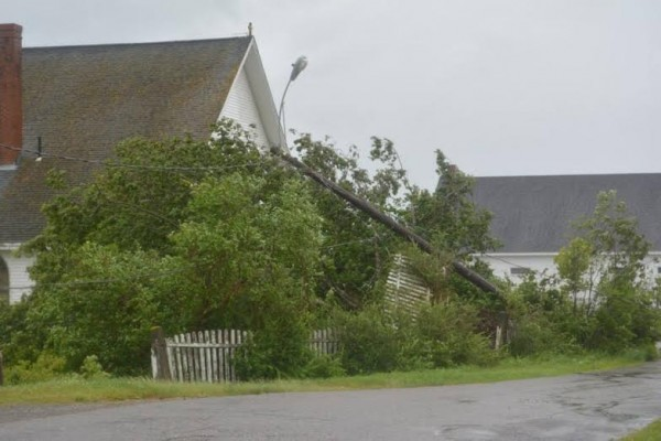 The weekend storm tossed a tree against Sacred Heart Catholic Church in Lubec, which was still experiencing widespread power outages on Monday.