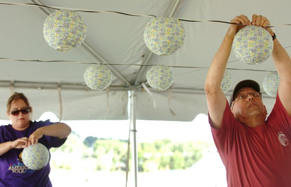 &quotIt always amazes me how an empty site becomes a festival so quickly,&quot said Roger Hicks (right) of Bangor as he volunteers setting up lights in the beer tent on Thursday, Aug. 26, 2010 in preparation for the American Folk Festival on the Bangor Waterfront.