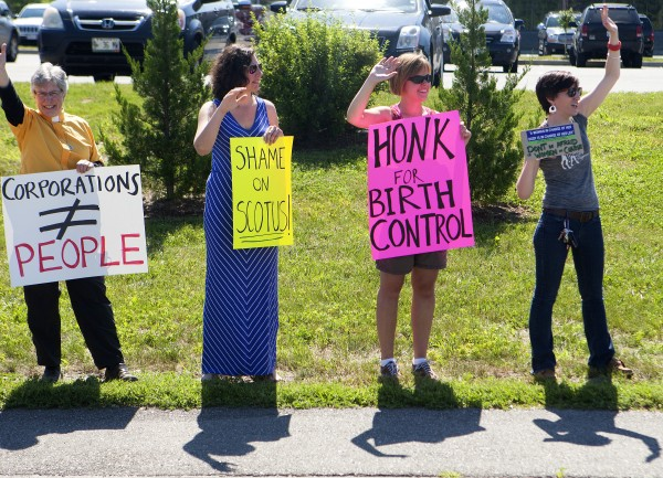 Protesters show their support for women's rights during a protest against the recent Supreme Court decision about birth control and Hobby Lobby on Saturday outside the Bangor Hobby Lobby.