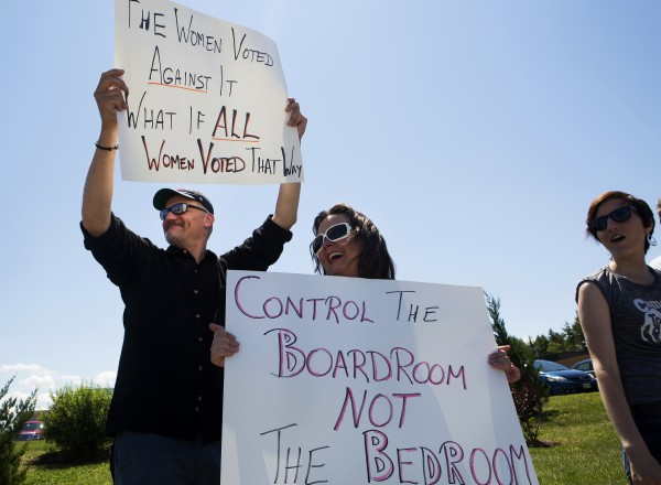 Duncan Dewyer (left) and Julie Jenkins hold up signs during a protest against the recent Supreme Court decision about birth control and Hobby Lobby on Saturday outside the Bangor Hobby Lobby.