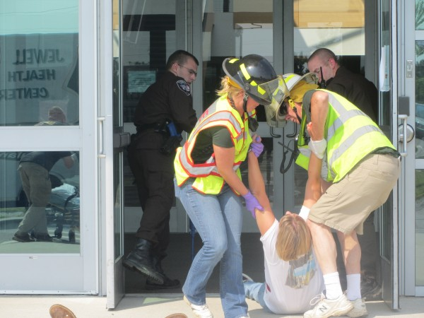 A person portraying a shooting victim is dragged out of the entrance to Mount View High School in Thorndike Saturday morning during an emergency drill.