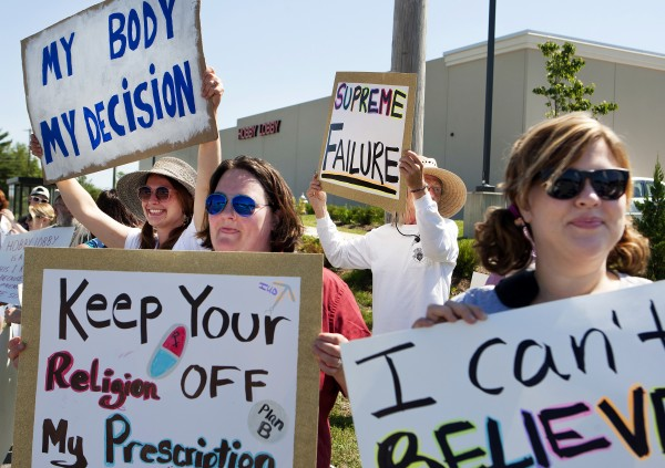 Protesters hold up signs during a protest against the recent Supreme Court decision about birth control and Hobby Lobby on Saturday outside the Bangor Hobby Lobby.