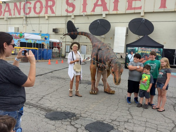 Adriene Berry of Alexander hides behind her mom, Clarissa Parker, as she takes a photo of &quotBuster,&quot a baby Tyrannosaurus rex at the Bangor State Fair posing with Gavin Berry, Acalia Berry, Austin Beach and Brandon McMannus.