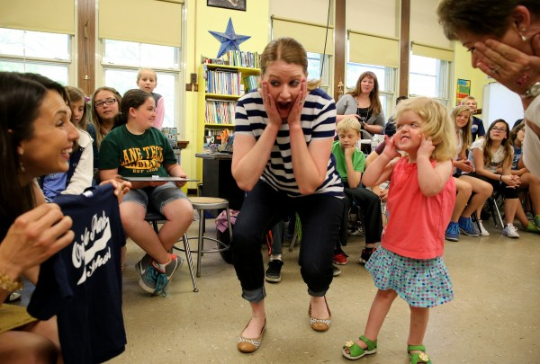 Kerry Lynch, center, and daughter Mary Cate Lynch, 2, and Mary Cate's grandmother, Maureen Ryan, right, react after Mary Cate is presented with a school shirt by teacher Michelle Reynolds, left, at Oriole Park Elementary School in Chicago on June 13, 2014.