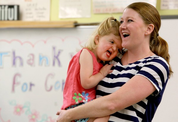 Kerry Lynch holds her daughter, Mary Cate Lynch, 2, at Oriole Park Elementary School in Chicago on June 13, 2014, to give a disability awareness presentation and teach compassion, as part of a national movement inspired by the book &quotWonder.&quot