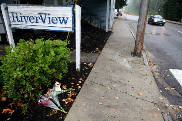 Bouquets and a stuffed dog lay in the mulch in front of the RiverView apartment complex in Saco Monday morning where a family of five was found shot to death inside on Sunday.