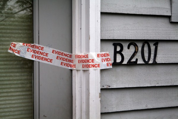 Police tape secures the door of unit B201 at the RiverView apartment complex in Saco on Monday. A family of five was found shot to death inside on Sunday.