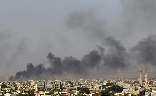Plumes of black smoke rise over the vicinity of Camp Thunderbolt, after clashes between militants, former rebel fighters and government forces in Benghazi on Saturday. The U.S. evacuated its embassy personnel from Libya on Saturday.